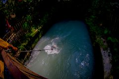 Above view of unidenfied peoplewalking over the hanging long metal bridge over the Seti river with high banks outside of. Pokhara in Nepal, Asia Royalty Free Stock Image