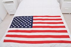 Above view of USA United States of American flag on white blanket. In bedroom with light interior. Happy Flag Day concept royalty free stock image