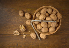 Above View of Walnuts grown in Oregon, in a Wooden Bowl on a Dark wood Table Background with some cracked and the nutcracker. Stock Photography