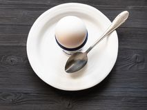 Egg in cup and spoon on white plate on dark table royalty free stock image