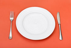 Above view of white plate, fork, knife on red Royalty Free Stock Photography