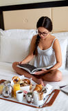 Above view of woman in bed wearing glasses reading. Royalty Free Stock Photo