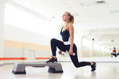 Above view of woman exercising step aerobics with dumbbells. Mid shot of woman exercising step aerobics with dumbbells Royalty Free Stock Photography