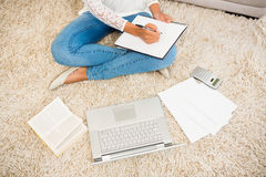 Above view of a woman writing note while using her laptop Royalty Free Stock Images