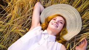 Above view young romantic red haired woman lying on wheat field and day dreaming. Above view of young romantic red haired woman in white cotton dress and big hat stock video