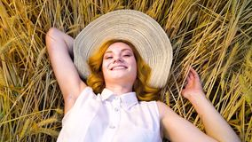 Beautiful girl lying on wheat field in harvest season. Above view of young woman in white cotton dress and straw hat lying on wheat field and smiling at camera stock video