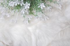 White Artificial Flower on White Puffy Fabric Background. Above of white artificial flower on white puffy fibers fabric background Royalty Free Stock Photos