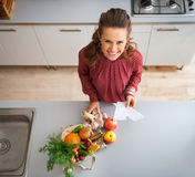 From above, woman smiling in kitchen with fall fruit and veg Stock Photo