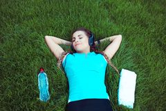 Relaxing fit woman lying on meadow royalty free stock photography