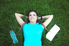 Relaxing fit woman lying on meadow royalty free stock images