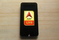 ABP News. App on smartphone kept on wooden table stock photo