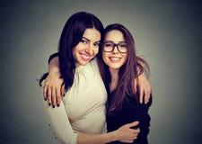 Abraçando as mulheres felizes que sorriem na câmera imagem de stock