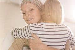 Abraçando a mãe que sofre da leucemia imagens de stock