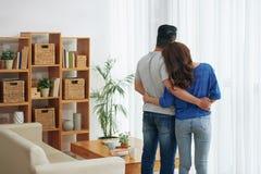 Abraçando os pares que estão na sala de visitas fotografia de stock royalty free