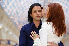 Abraçando pares - homem escuro-de cabelo e mulher vermelho-de cabelo Fotografia de Stock