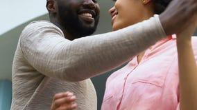 Abraço afro-americano dos pares, feliz junto, anticipando, futuro planeando filme