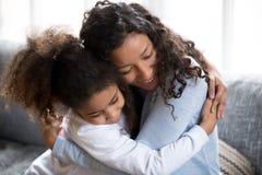 Abraço afro-americano feliz da mamã e da filha que faz a paz fotos de stock