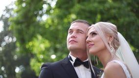 Abraço considerável do noivo sua noiva bonita Recém-casados que andam no parque Mulher do cabelo louro no vestido de casamento el filme
