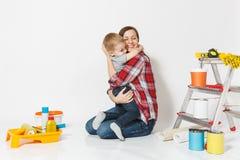 Abraço da mãe seu filho pequeno Instrumentos para a sala do apartamento da renovação isolada no fundo branco Papel de parede, col imagens de stock royalty free