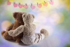 Abraço de dois ursos da peluche com suas partes traseiras ao visor Na parede o cair de papel dos corações Cartão d do dia do ` s  Imagens de Stock Royalty Free