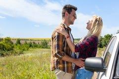 Abraço do amor dos pares que olha a cara perto da estrada do campo do carro Fotografia de Stock Royalty Free