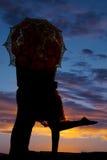 Abraço do homem e da mulher atrás da silhueta do guarda-chuva Imagem de Stock