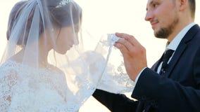 Abraço dos noivos em uma caminhada do casamento contra o lago filme