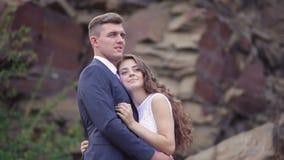 Abraço dos noivos em uma caminhada do casamento no fundo da montanha filme