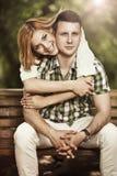 Abraço novo feliz dos pares e assento de sorriso no parque Fotografia de Stock Royalty Free