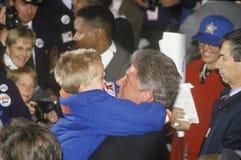 Abraços de Bill Clinton do regulador uma criança em uma reunião da campanha de Denver em 1992 em seu dia final da campanha em Den imagens de stock