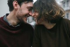 Abraços e riso dos pares do vintage Copos de café e feijões de café frescos ao redor Fotos de Stock