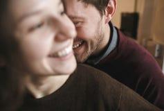 Abraços e riso dos pares do vintage Copos de café e feijões de café frescos ao redor Fotos de Stock Royalty Free