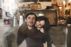 Abraços e riso dos pares do vintage Copos de café e feijões de café frescos ao redor Imagens de Stock Royalty Free