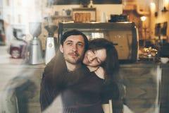 Abraços e riso dos pares do vintage Copos de café e feijões de café frescos ao redor Imagem de Stock Royalty Free