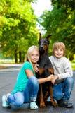 Abraços louros cão amado ou doberman da menina e do menino Imagem de Stock Royalty Free