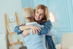Abraços mornos de uma jovem mulher alegre e de sua avó fotografia de stock royalty free