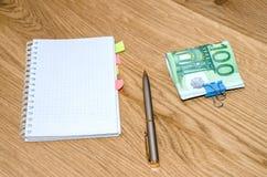 Abra al planificador diario con la pluma de bola, cientos billetes de banco euro en la tabla de madera Fotos de archivo