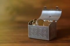 Abra a arca do tesouro enchida com as moedas no fundo de madeira fotografia de stock