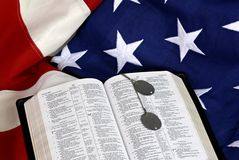 Abra a Bíblia com os Tag de cão na bandeira dos E.U. Fotografia de Stock