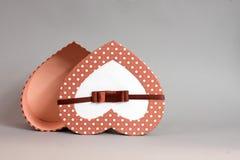 abra a caixa de presente na forma do coração no fundo cinzento imagens de stock