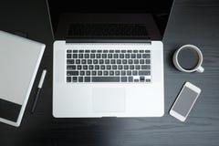 Abra a caneca do portátil, de tabuleta gráfica, de smartphone e de café em um blac Imagem de Stock