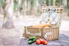 Abra a cesta do piquenique com tomates, pepinos e pão sobre uma tabela de madeira no parque Foto de Stock Royalty Free