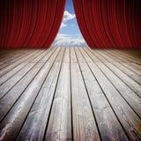 Abra cortinas vermelhas do teatro e o assoalho de madeira contra um céu nebuloso Imagens de Stock Royalty Free