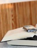 Abra densamente el libro y el teléfono Foto de archivo