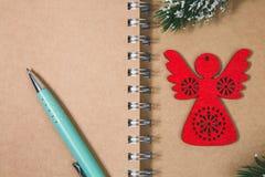 Abra el ángel de madera rojo de la libreta espiral en blanco y metal la pluma Imágenes de archivo libres de regalías