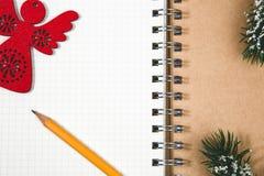 Abra el ángel de madera rojo y el lápiz de la libreta espiral en blanco Imagenes de archivo