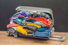 Abra el bolso con ropa, cámara del viaje de la película en piso Foto de archivo libre de regalías