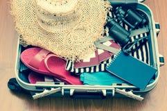 Abra el bolso del viaje con ropa y accesorios en backgroun de madera Fotografía de archivo