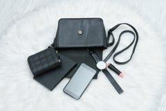 Abra el bolso negro con el teléfono móvil, el reloj, el lipstik y la PU caídos Imagenes de archivo
