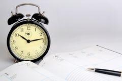Abra el calendario y el reloj de alarma Imágenes de archivo libres de regalías